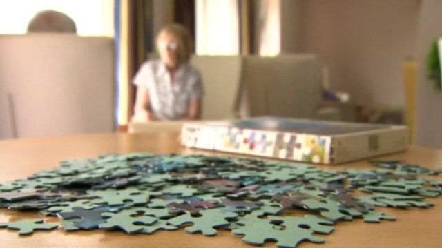 Jigsaw in foreground with older people on chair out of focus in the background