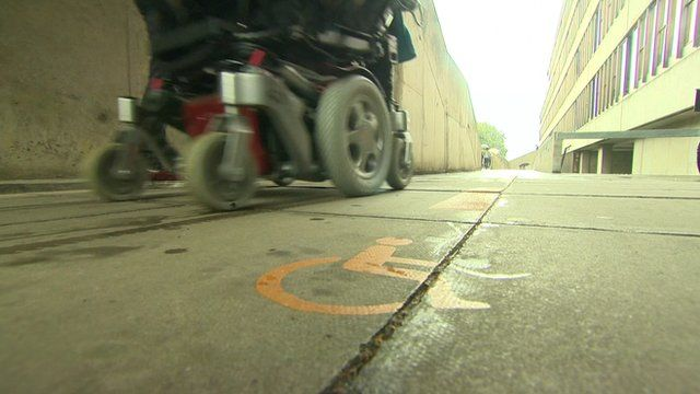 Person in an electric wheelchair going past a disabled sign on the ground