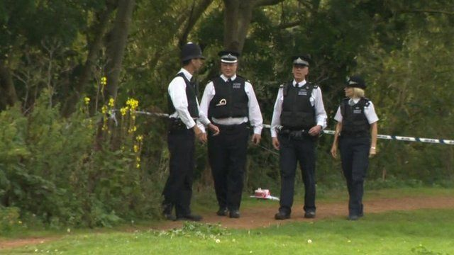 Police in front of police cordon in park where Alice Gross search is taking place