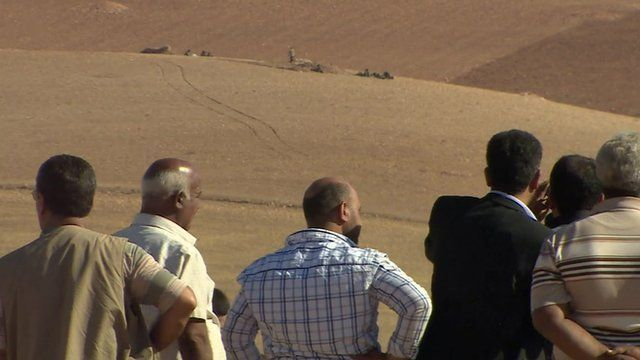 Kurdish villagers overlooking IS militants