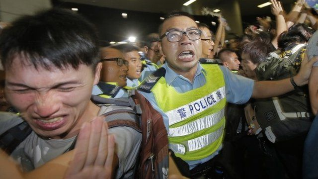 A protester, left, reacts after police officers used pepper spray against protesters attempting to break into government building