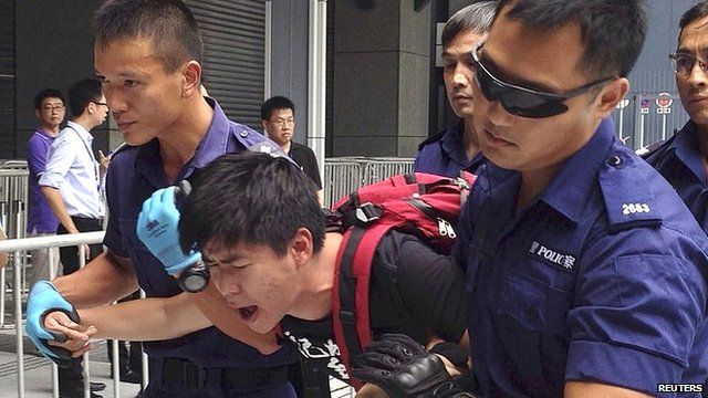 A protester is taken away by police after storming into government headquarters in Hong Kong