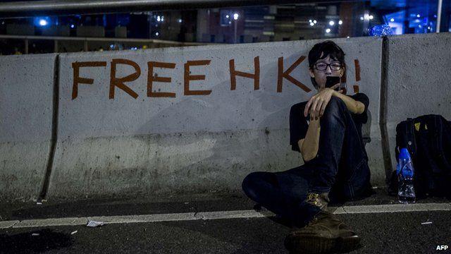 A Hong Kong pro-democracy protestor rests and checks his phone