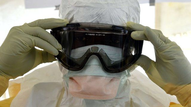 A health workers in protective suit puts glasses on