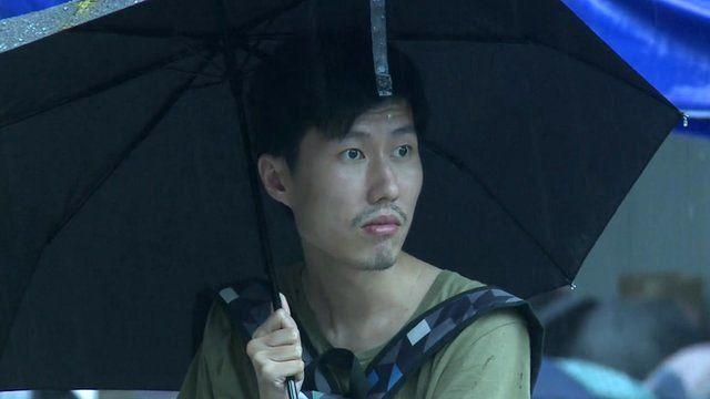 Hong Kong protester watching rain from under large umbrella