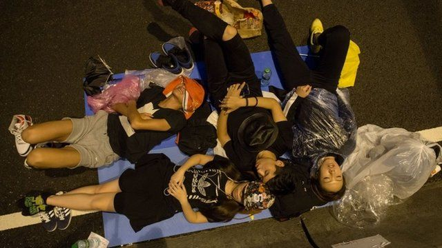 Protesters sleep on a road outside the Central Government Office in Hong Kong on October 5, 2014