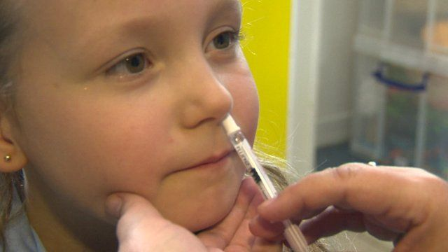 Child receiving vaccine in nostril