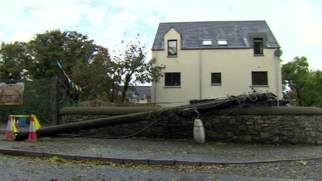 Fallen telegraph pole in front of a house