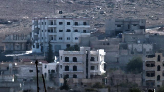 Black IS flag raised above Kobane, Syria