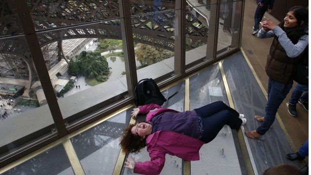A visitor takes a photo on the new floor at The Eiffel Tower