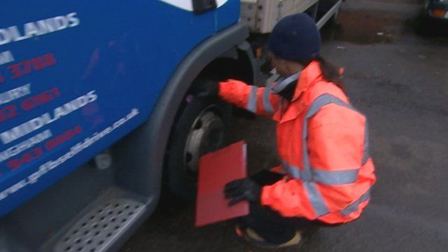 Man checking lorry tyre