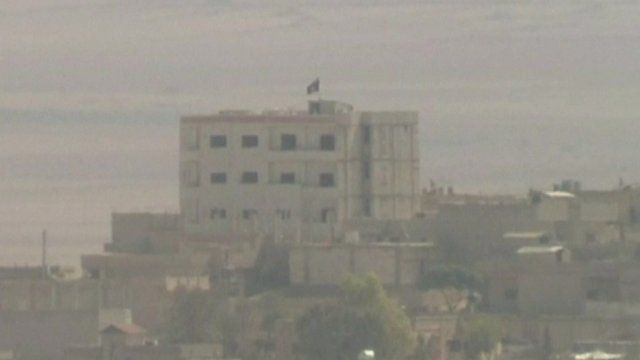 Building in Kobane with IS flag raised above it