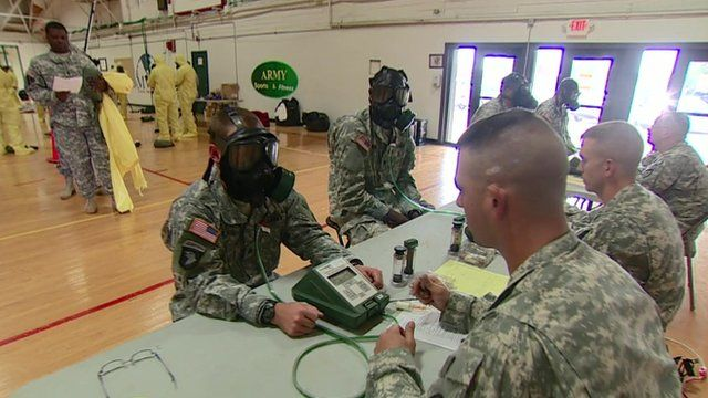 US troops being kitted out with gas masks and protective suits