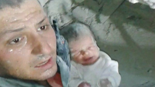 Khaled Harrah with a 10-day old baby rescued from rubble
