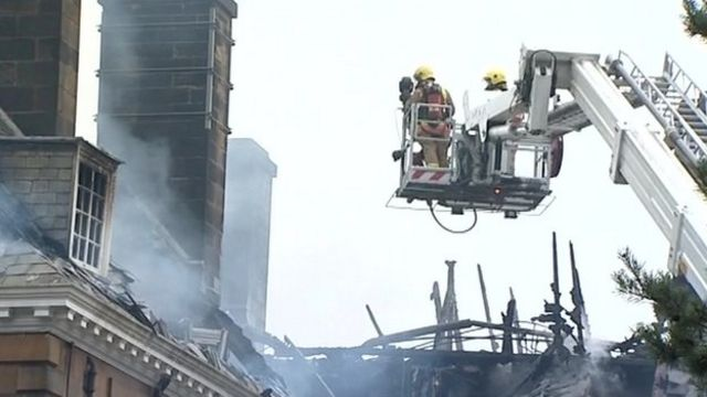 Firefighters on a crane assess the roof damage at Crathorne Hall