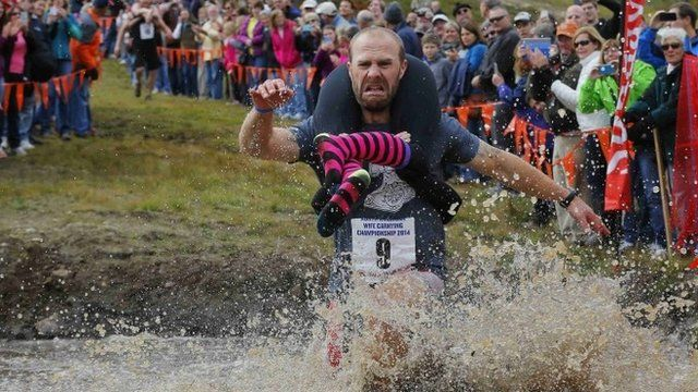 Eventual winners Jesse Wall carries Christina Arsenault through the water pit while competing in the North American Wife Carrying Championship at Sunday River ski resort in Newry, Maine October 11, 2014