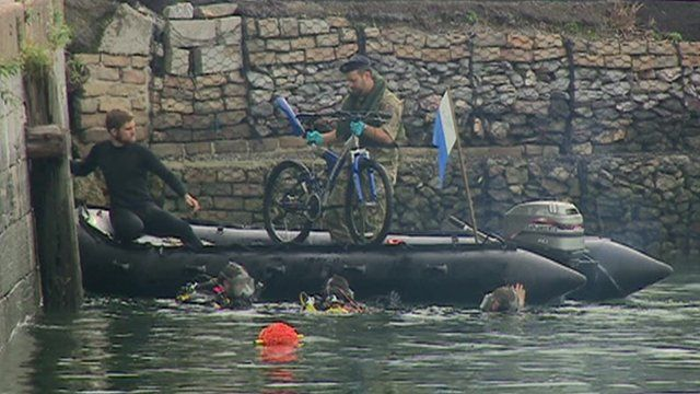 Two men in an inflatable boat pull a bicycle out of the harbour