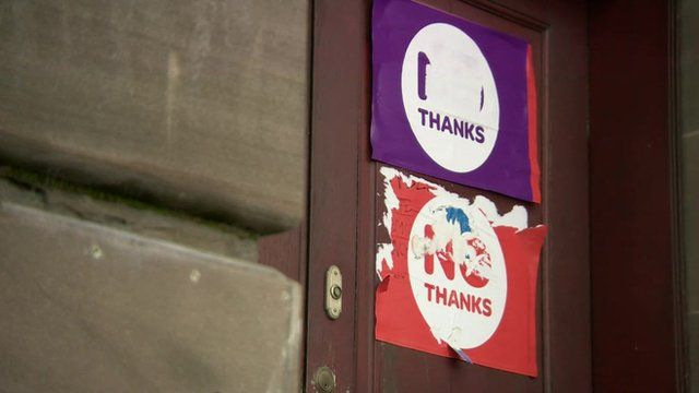 Two faded 'No thanks' posters stuck on a door