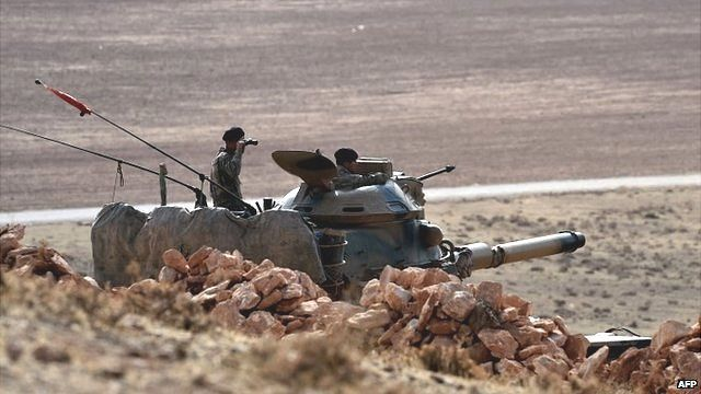 Turkish soldiers stationed on a hill facing the Syrian town of Kobane