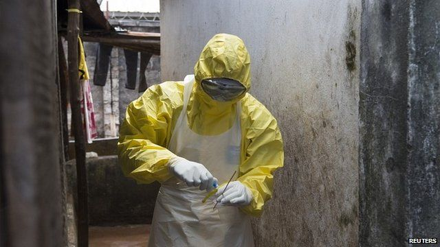 A health worker with a sample from a suspected Ebola fatality, Freetown, Sierra Leone (13 October)