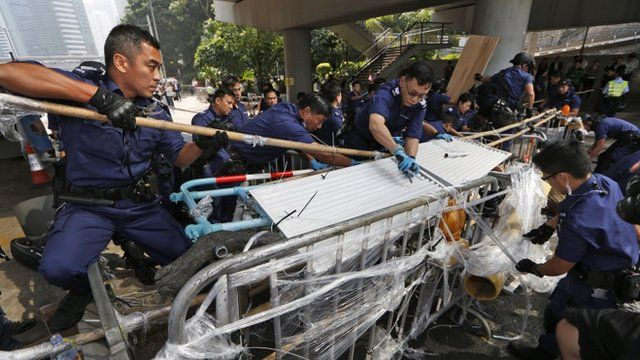 Police officers remove barricades that protesters set up to block off main roads in Central district in Hong Kong