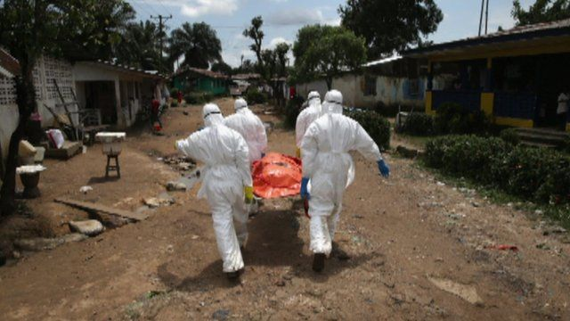 Four health workers in protection suits carry a body in an orange body bag
