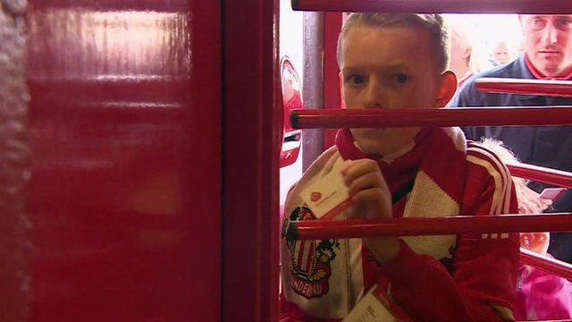 A young Sunderland fan walking through the turnstile, ticket in hand