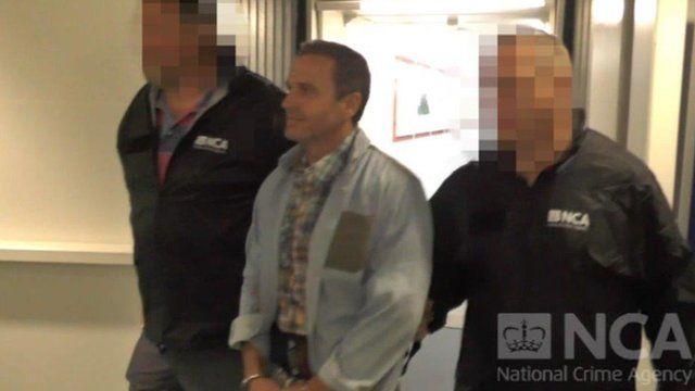 Martin Evans being escorted through Heathrow airport