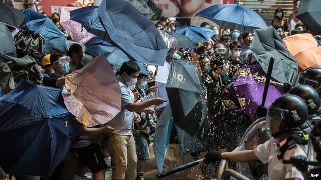 Police use pepper spray against pro-democracy protesters using raised umbrellas for protection during a clash in the Mongkok district of Hong Kong late on 17 October 2014
