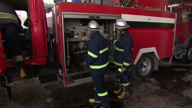 Two Iraqi fire-fighters examine their fire engine