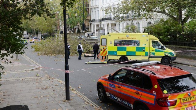 Police and London Ambulance services in Kensington, west London where a woman has died after a tree fell into the street during high winds caused by the remnants of Hurricane Gonzalo