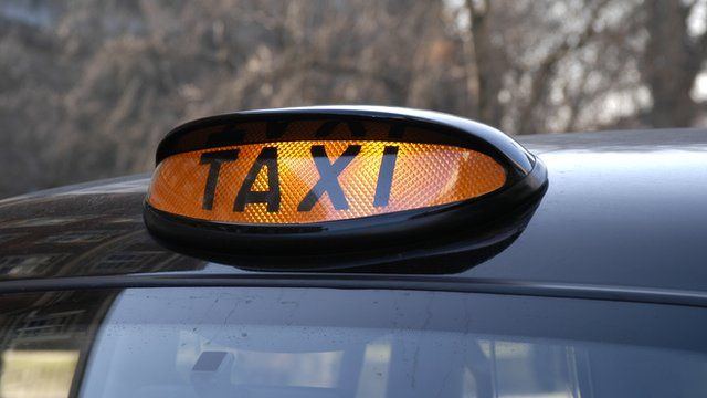 A black cab with its orange light on
