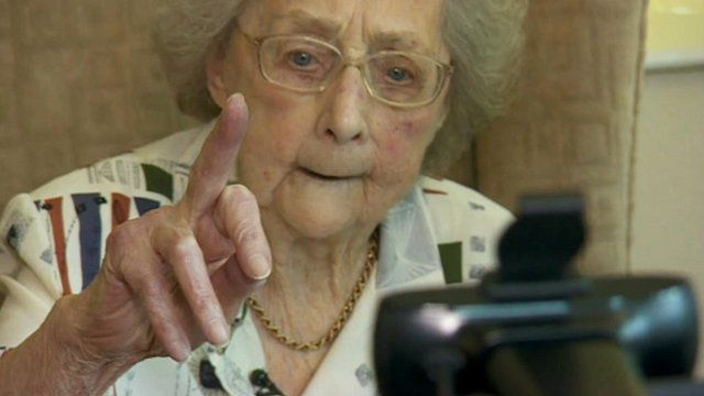 Dorothy Casford holds up finger at video device