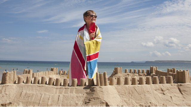 young boy on holiday building sandcastle