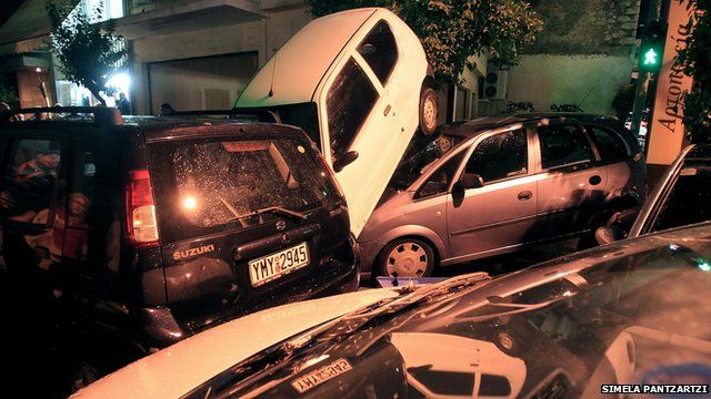 Piled up vehicles in a street in Athens, Greece, after torrential rain caused flash flooding