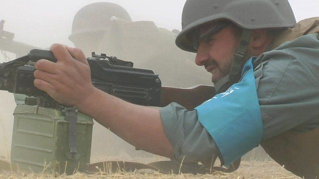 Member of the security forces in Baghlan Province lying on ground with gun