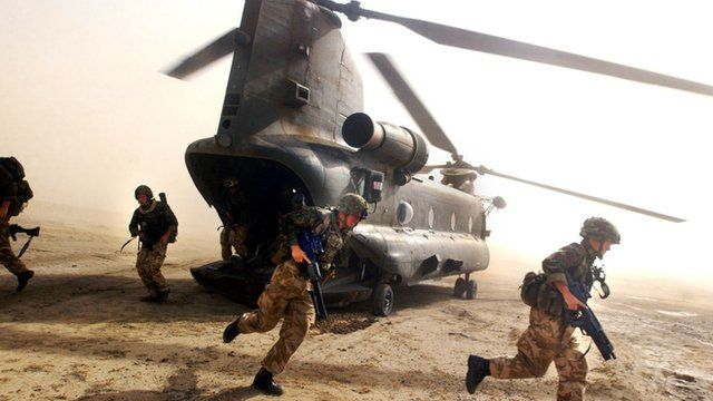 British Royal Marines of 45 Commando scramble out the back of a Chinook helicopter during an eagle vehicle check point (VCP) operation as part of the ongoing Operation Buzzard July 8, 2002 in southeastern Afghanistan