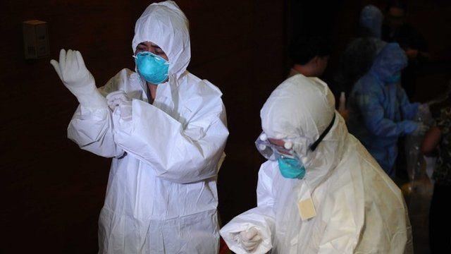 Philippine health workers don personal protective equipment (PPE) suits during training by hospital management personnel regarding the Ebola virus at the Research Institute for Tropical Medicine in Alabang town in Manila on October 28, 2014