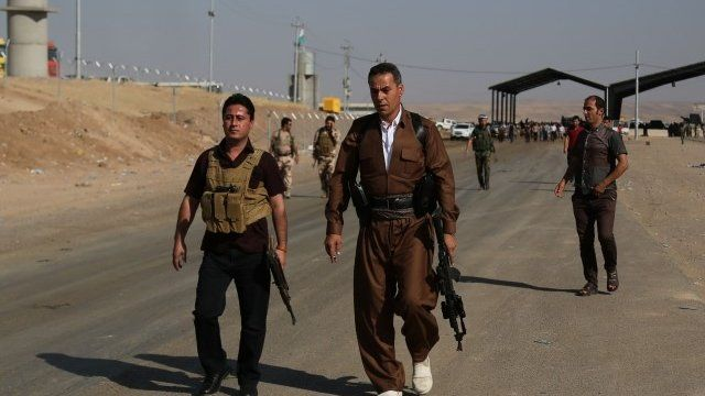 Kurdish Peshmerga fighters walk towards the front line at the Khazer checkpoint outside of the city of Irbil in northern Iraq,