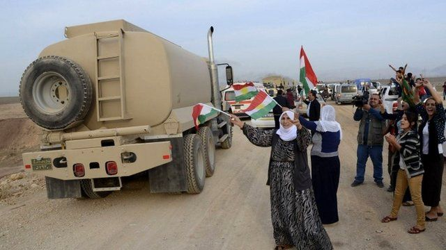 A convoy of peshmerga vehicles is welcomed by Turkish Kurds after crossing into Turkey