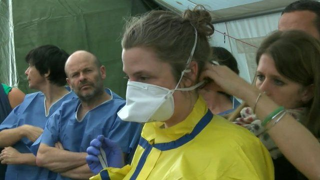 A healthcare worker being dressed in a protective suit