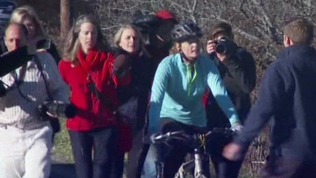 Kaci Hickox on bike ride surrounded by press