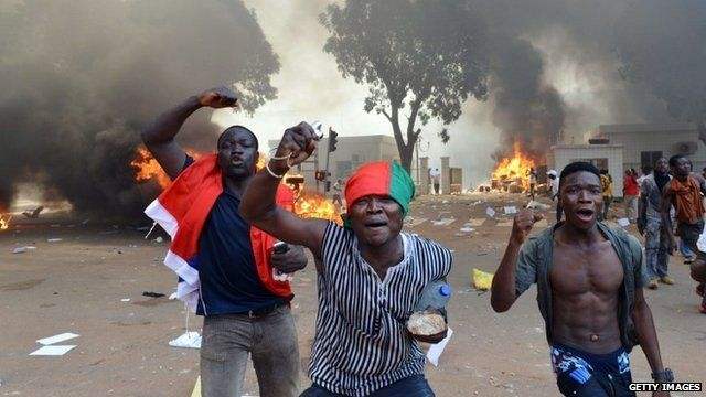 Men in front of burning cars, near the Burkina Faso's Parliament