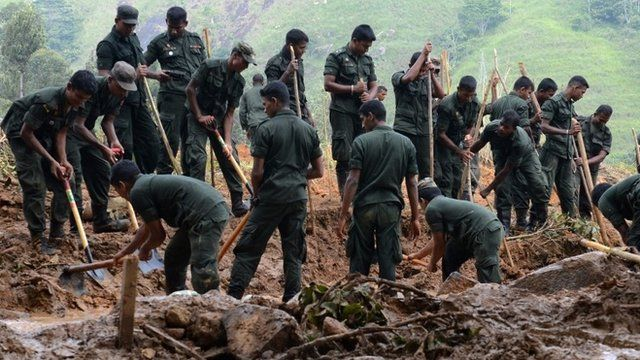 Sri Lankan military personnel dig during a search operation at the site of a landslide caused by heavy monsoon rains in Koslanda village in central Sri Lanka on November 1, 2014