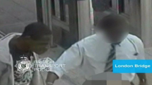 CCTV shot of the alleged attacker on the left next to a member of station staff (face blurred out)