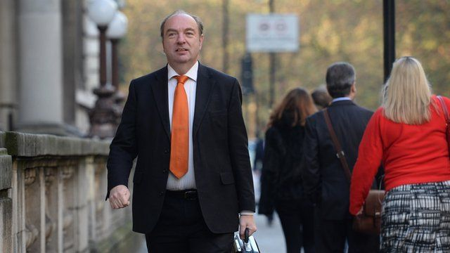 Norman Baker walking along the street, carrying a briefcase