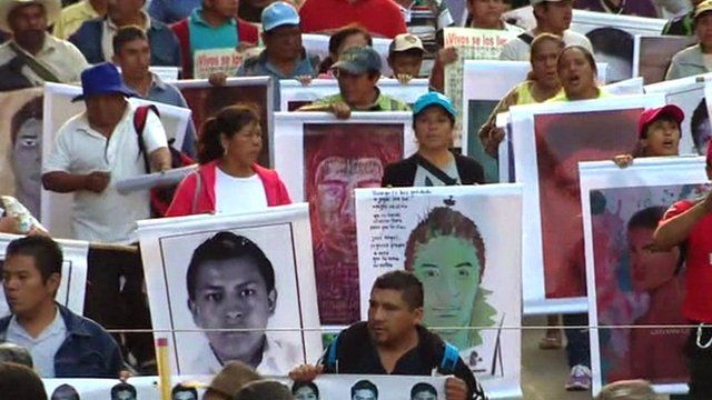People march holding posters of the missing students
