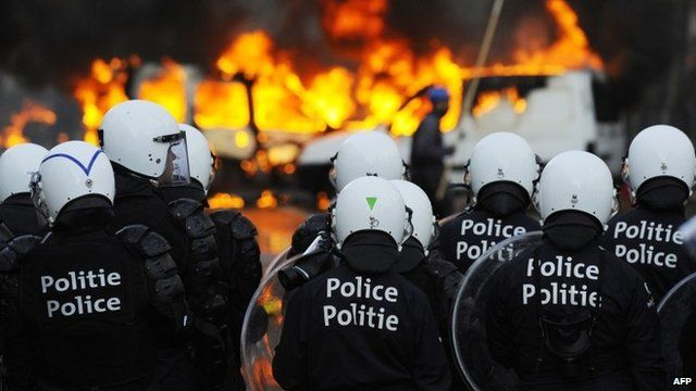 Riot police and burning vehicles