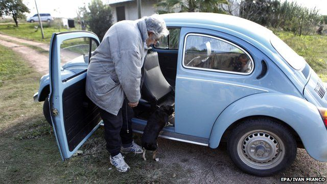 Uruguay's President Jose Mujica helping his pet dog climb into the presidential Volkswagen Beetle