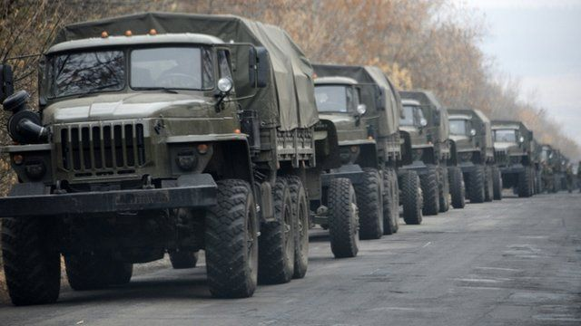 Unmarked military vehicles parked on a road outside the separatist rebel-held eastern Ukrainian town of Snizhne